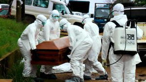 Burial team workers handling a casket with the human remains 的 an Ebola victim in Monrovia. Photo credit: Alexander Wiaplah